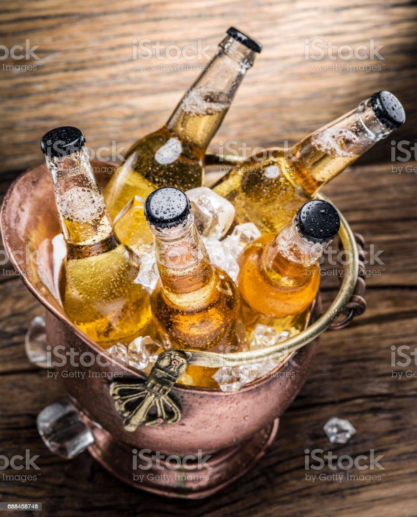 Frias garrafas de cerveja no balde descarado na mesa de madeira. - foto de acervo