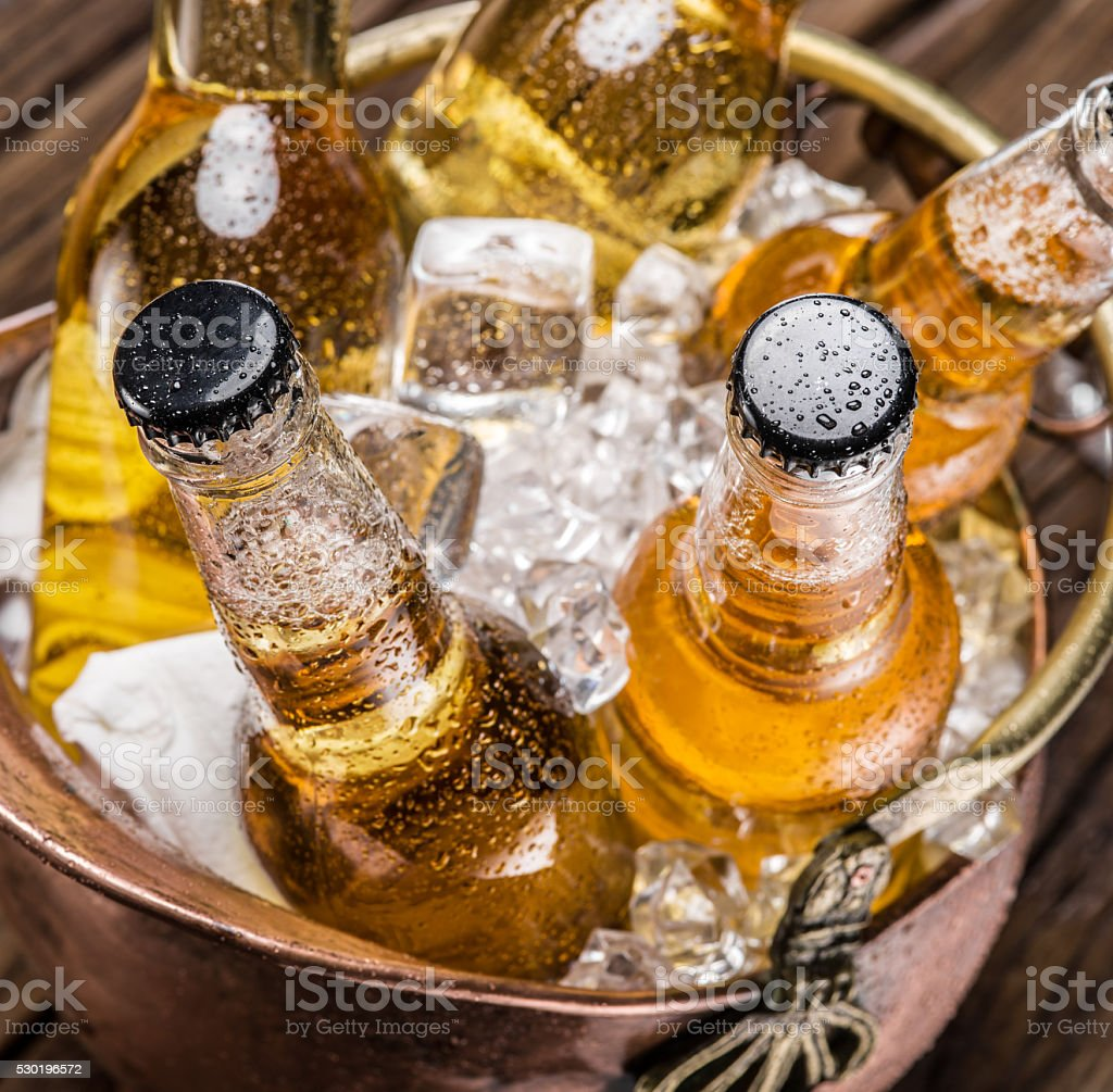 Cold bottles of beer in the brazen bucket. stock photo