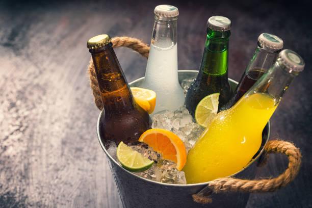 froids bouteilles de boissons diverses dans le bac à glaçons - boisson rafraîchissante photos et images de collection