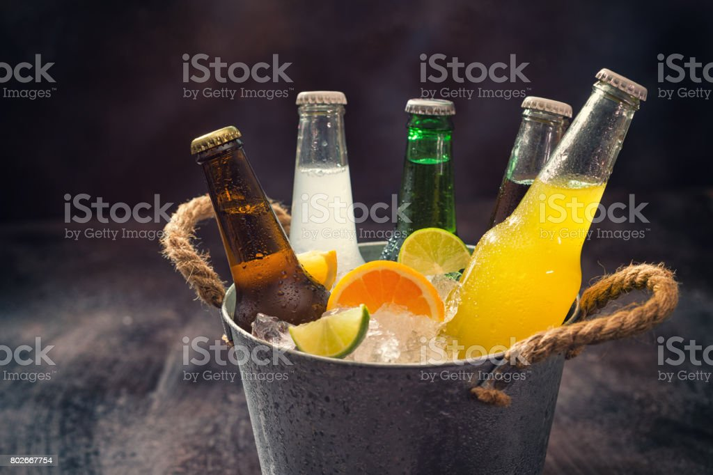 Frío botellas de diferentes bebidas en el cubo de hielo - foto de stock