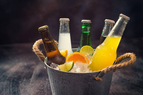 cold bottles of various drinks in the ice bucket - bottle soft drink foto e immagini stock