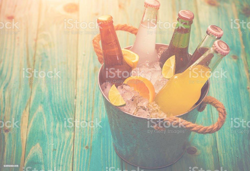 Frias garrafas de várias bebidas no balde de gelo - foto de acervo