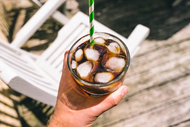 cold brew coffee outside in the garden on a sunny summers day. - iced coffee stock pictures, royalty-free photos & images