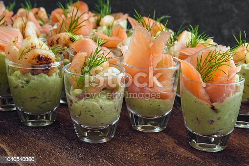 cold buffet with appetizers in glasses, prawn shrimps and salmon on avocado cream and dill garnish on dark wood, selected focus, narrow depth of field