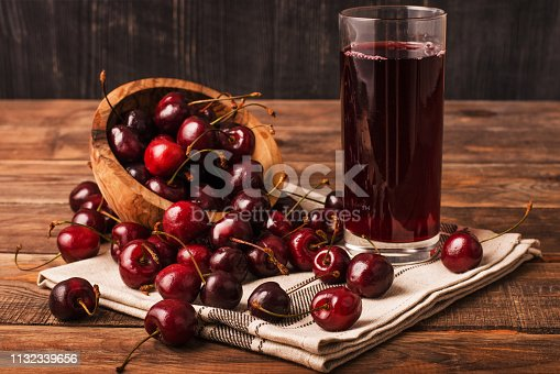 Cold cherry juice in a glass with ripe berries in bowl basket on a wooden table