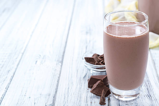 Cold Chocolate Milk Cold Chocolate Milk drink (close-up shot) on wooden background chocolate milk stock pictures, royalty-free photos & images