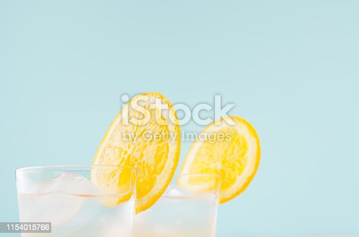 Cold citrus  beverage with orange, alcohol, ice in misted shot glass on green  background, closeup, top, edge, details.