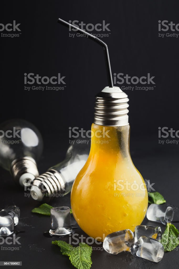 Cold cocktail in light bulb shaped glass on black background royalty-free stock photo