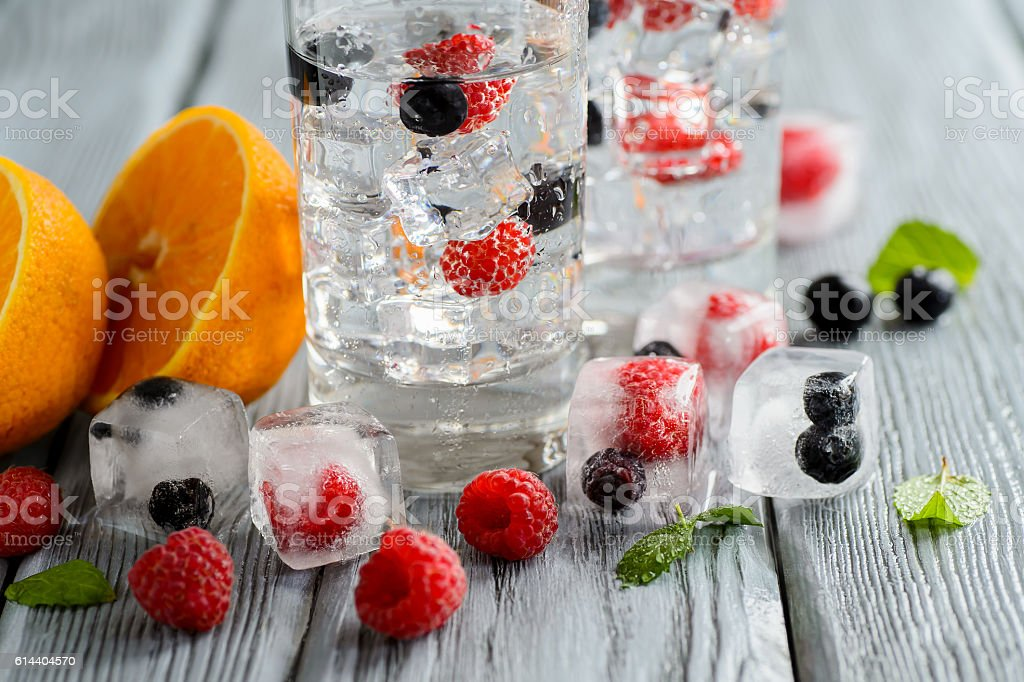 Cold cocktail with forest berries, frozen in ice cubes stock photo