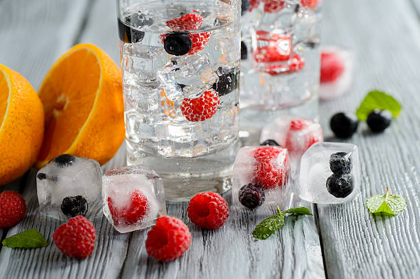 cold cocktail with forest berries, frozen in ice cubes - frozen berries stock photos and pictures