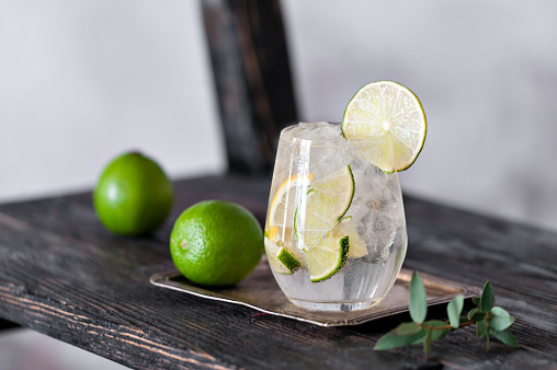 Cold cocktail with lime, lemon, tonic, vodka and ice