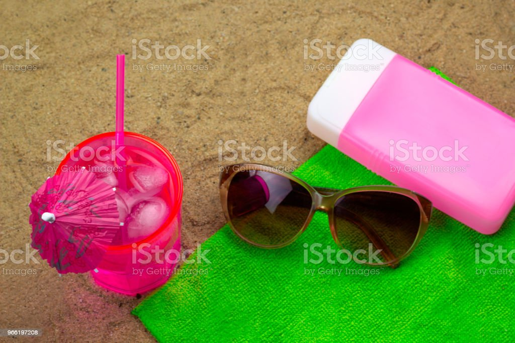 cold coctail,sunglasses and sunblock on a green towel on a bech stock photo