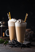 Cold coffee drink frappe or frappuccino, with whipped cream and chocolate chips, with straws over dark background