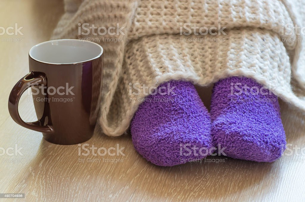 Cold concept with teacup near the legs stock photo