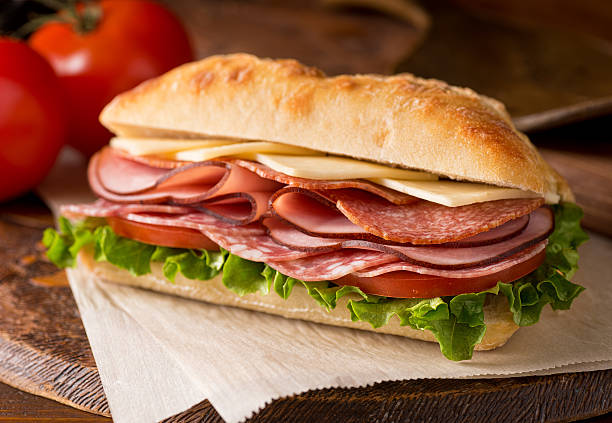 Cold Cuts Sandwich A delicious sandwich with cold cuts, lettuce, tomato, and cheese on fresh ciabatta bread. submarine sandwich stock pictures, royalty-free photos & images