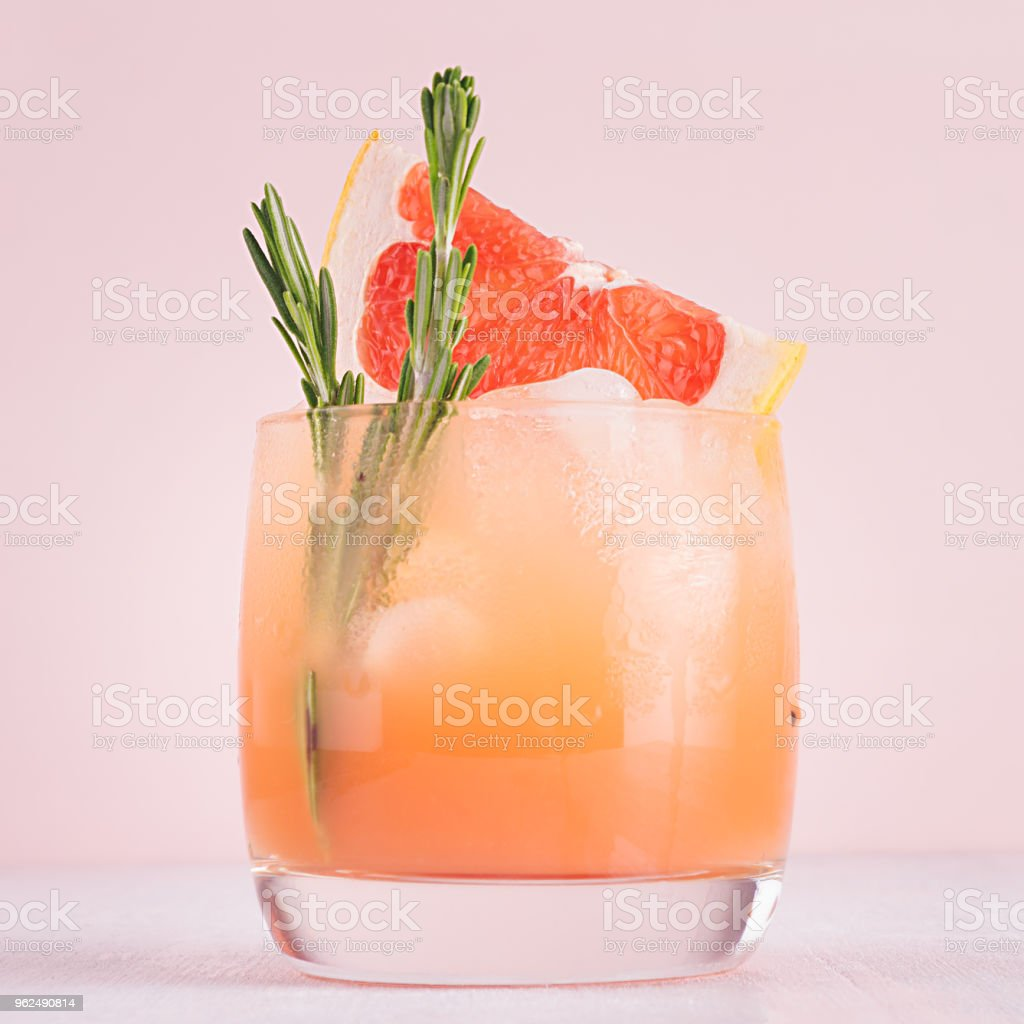 Cold detox cocktail of grapefruit juice with ice, rosemary, slices citrus on soft light pink and white background. - Royalty-free Affectionate Stock Photo