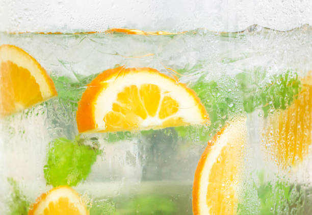 슬라이스 오렌지와 민트 잎, 냉 해독 물 배경. - 레모네이드 뉴스 사진 이미지