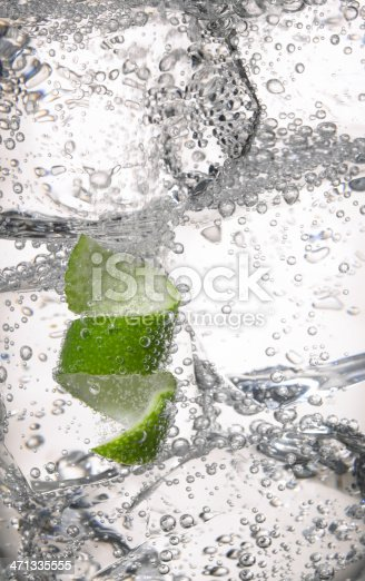 Close up of clear cold drink, ice cubes and lime peel