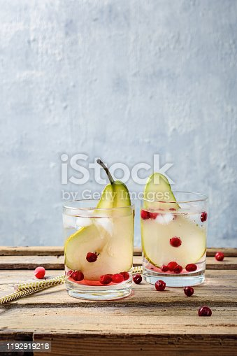 Cold drink tonic with pear and cranberries on a wooden background.