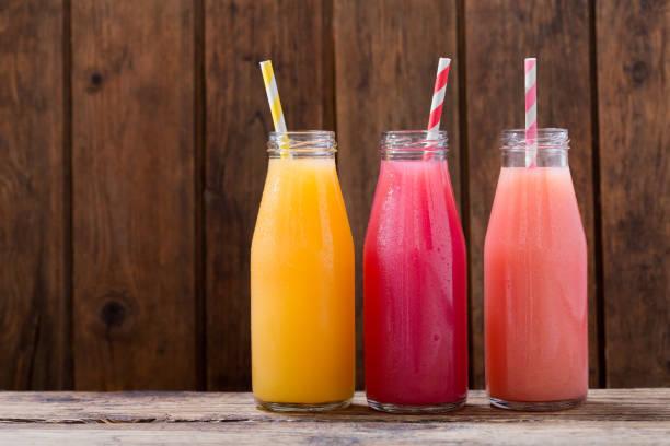 나무 테이블에 botlles에서 차가운 음료 - 주스 뉴스 사진 이미지