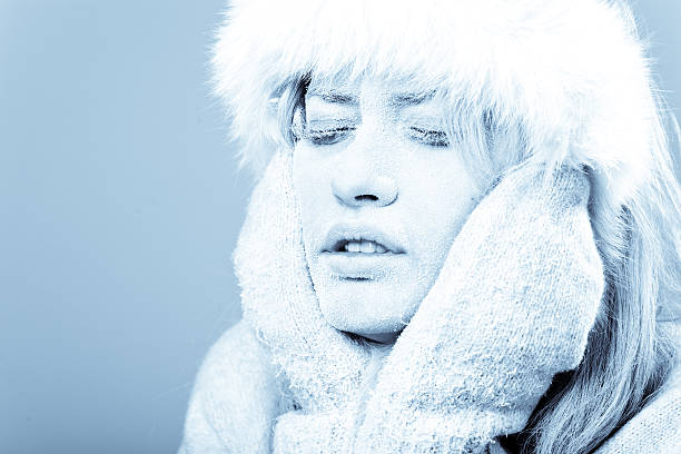 Cold female holding her face which is covered in ice stock photo