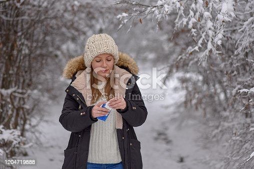 Cold flu winter season, runny nose. Showing sick woman sneezing at winter park