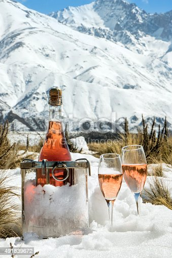Bottle and glasses of rosé champagne, at foot of the snowy Alps. France.
