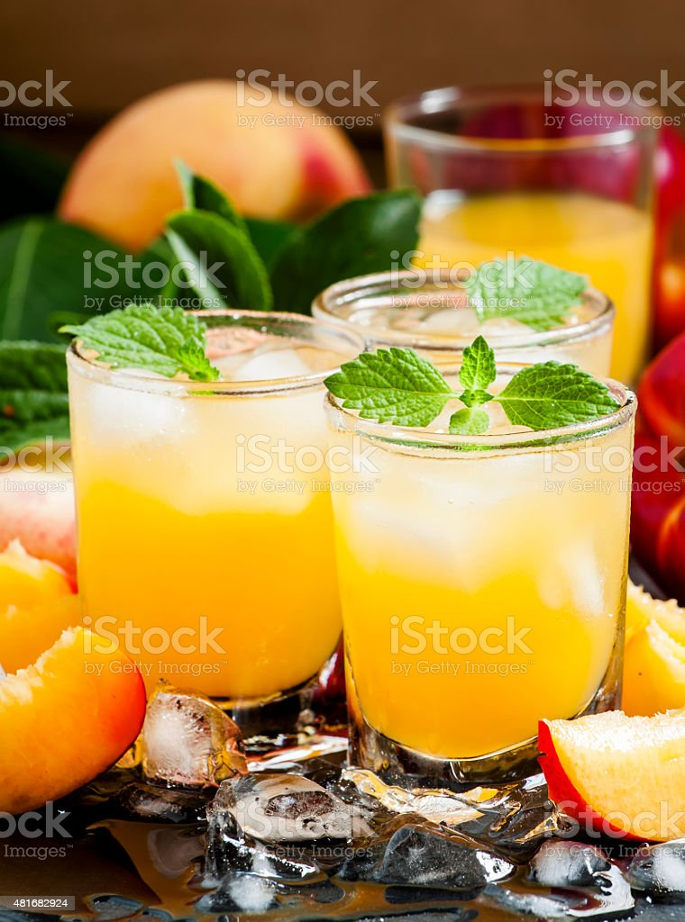 Cold fresh peach nectar with pulp, ice and mint stock photo