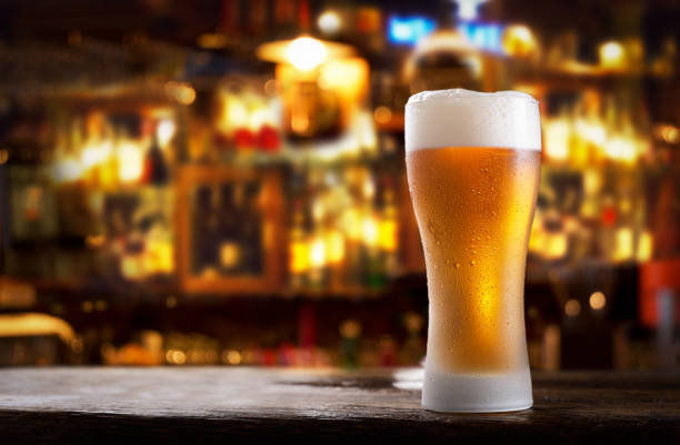 cold glass of beer in a bar on a wooden table stock photo