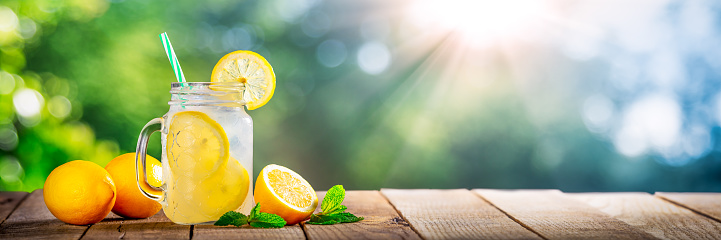 Cold Glass Of Lemonade On Wooden Table With Lemons, Tea Leaves And Sunlight