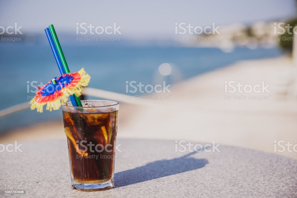 Cold glass of Malibu Cola stand on table near the sea stock photo
