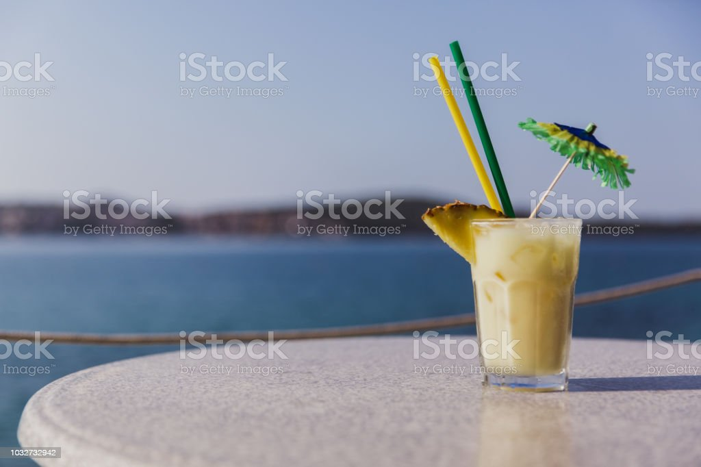 Cold glass of Pina Colada stand on table near the sea stock photo