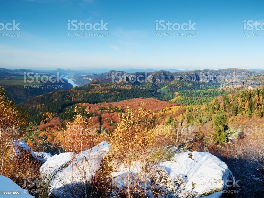 Cold golden spring daybreak. Snow on ground. Peaks of forests increased from mist stock photo