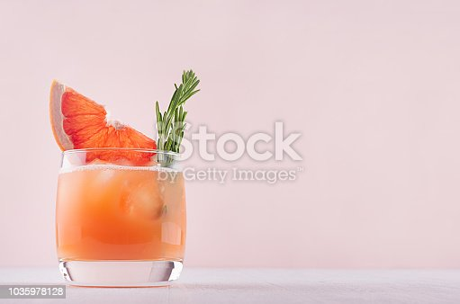 istock Cold grapefruit cocktail decorated twig rosemary and slice citrus on pink background. 1035978128