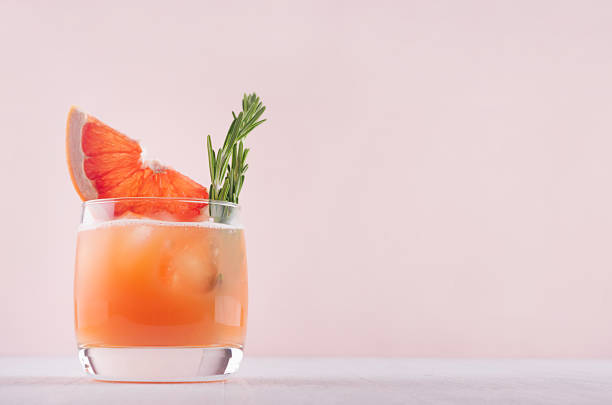 cold grapefruit cocktail decorated twig rosemary and slice citrus on pink background. - grapefruit cocktail stock photos and pictures