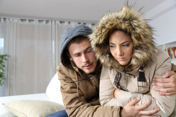 Cold home with an angry couple Cold home with an angry couple warmly clothed hugging sitting on a sofa in the living room warm clothing stock pictures, royalty-free photos & images