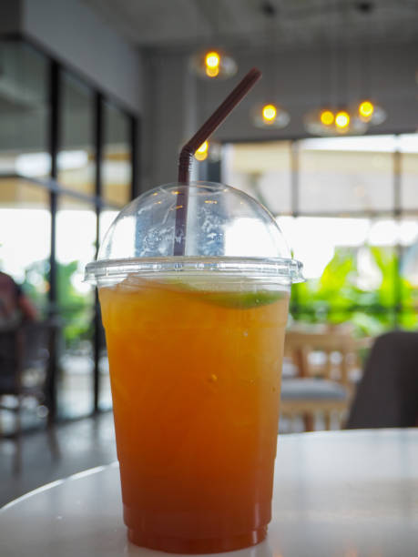 cold iced tea with lemon and straw in takeaway plastic cup. stock photo