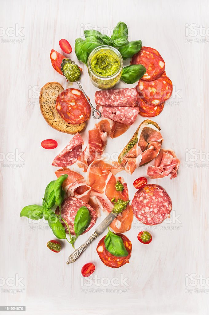 Cold  Italian meat plate with ham, sausage, bread and pesto stock photo