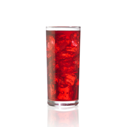 Tall glass of fruit juice full of ice