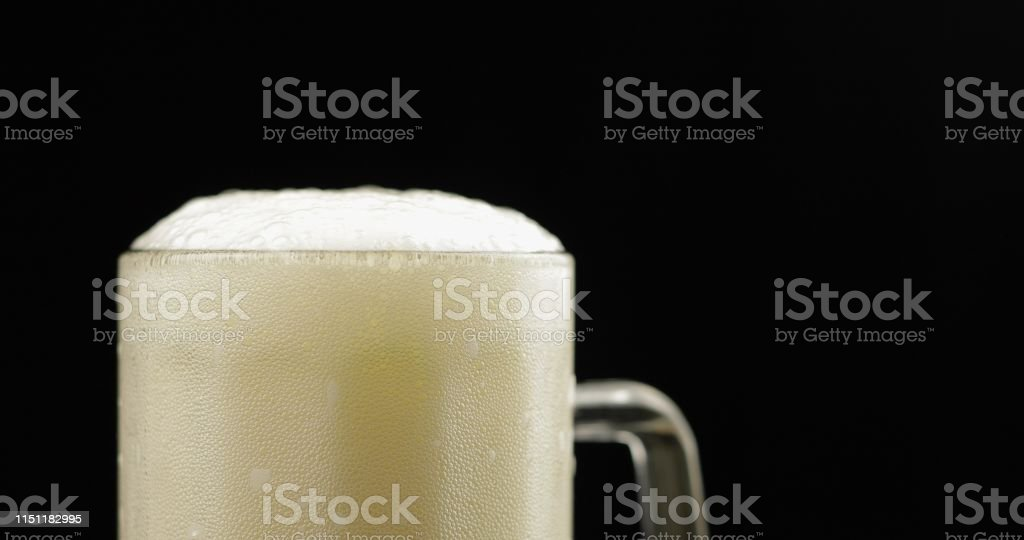 Cold Light Beer in a glass. Craft Beer foam close-up. Black...