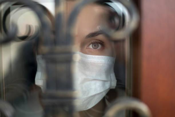 Mirada fría de una chica a través de la puerta principal de una casa durante la cuarentena - foto de stock