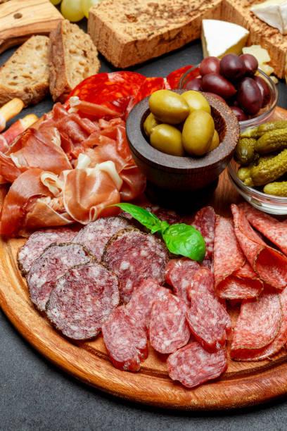 aufschnitt-platte mit salami, chorizo-wurst und schinken-schinken - brotschneidebrett stock-fotos und bilder