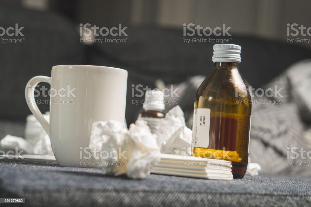 Medicinas para el resfriado, jarabe para la tos, bebida caliente, toallas de papel y tejidos a ritmo enfermedad, fiebre o gripe. Conseguir kit bien en mesa o sofá cama. Ser enfermo o enfermando o cogido frío o tener virus concepto. - foto de stock