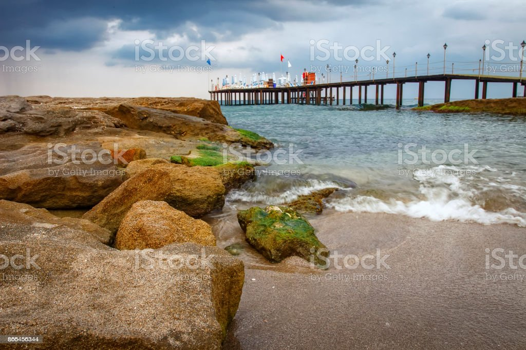 Cold morning seascape with rocky beach and pier, Konakli Turkey. stock photo