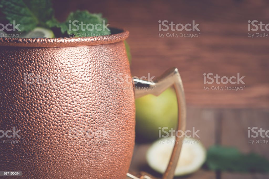 Cold Moscow Mule cocktail in copper mug on the rustic background stock photo