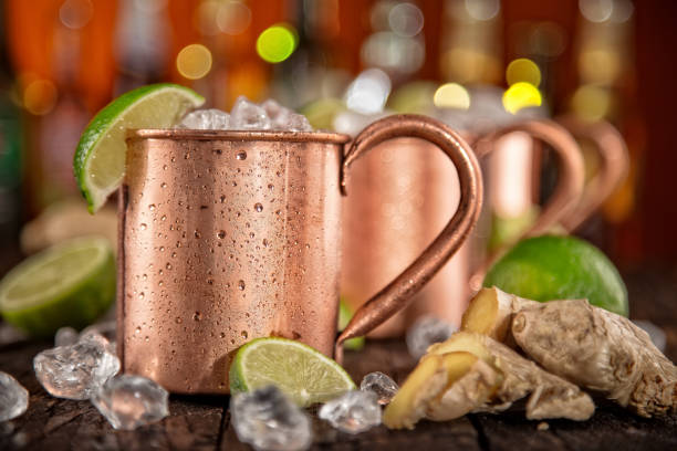 Cold Moscow Mules - Ginger Beer, lime and Vodka on bar Cold Moscow Mules - Ginger Beer, lime and Vodka on bar, close-up. mule stock pictures, royalty-free photos & images