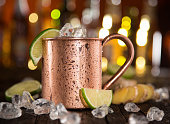 Cold Moscow Mules - Ginger Beer, lime and Vodka on bar, close-up.