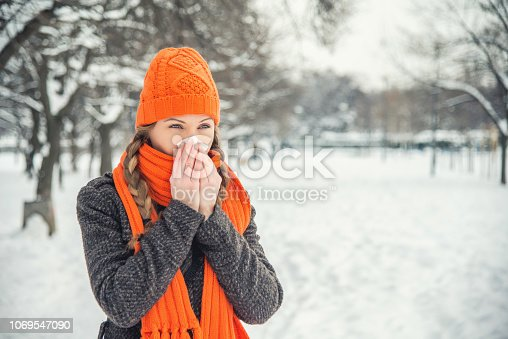 A young woman with braided long blond hair is outdoors in a park during the winter. There is snow and trees in the background. She is wearing winter clothes, an orange hat and scarf, and is blowing her nose with a handkerchief / hanky / tissue. She is looking away from the camera. With copy space.
