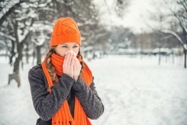 Cold A young woman with braided long blond hair is outdoors in a park during the winter. There is snow and trees in the background. She is wearing winter clothes, an orange hat and scarf, and is blowing her nose with a handkerchief / hanky / tissue. She is looking away from the camera. With copy space. human parainfluenza virus stock pictures, royalty-free photos & images