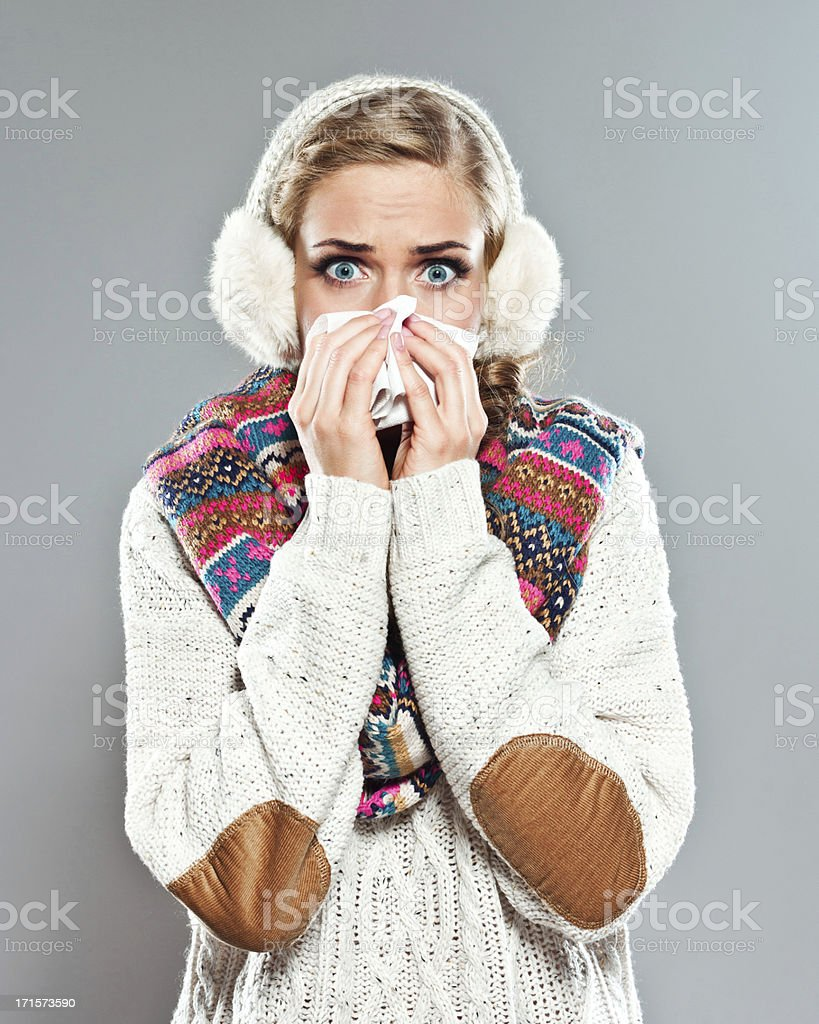Cold Portrait of a young adult woman wearing a sweater, earmuffs and scarf blowing nose. Studio shot on the gray background. 20-24 Years Stock Photo